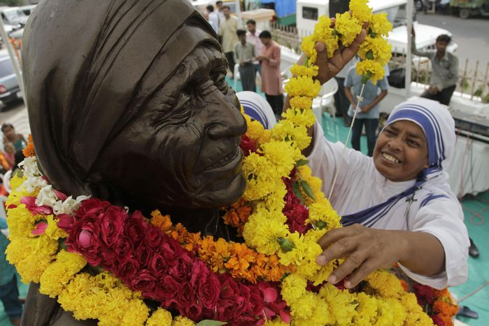 A nun of the Missionaries of Charity puts a garland around a bust of Mother Teresa, the founder of the order, during celebrations to mark her birth centenary, in Ahmadabad, India, Thursday, Aug. 26, 2010. Special feasts to feed the poor, a festival of films on her life and work, the launch of a new train called the Mother Express, and interfaith prayer meetings were among events planned to mark the yearlong anniversary. (AP Photo/Ajit Solanki)