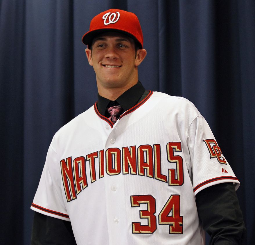 ASSOCIATED PRESS Bryce Harper, smiles at his family after putting on the jersey and hat, at a news conference where the Washington Nationals baseball team introduced him as their first overall selection in the 2010 First-Year Player Draft, at Nationals Park in Washington Thursday, Aug. 26, 2010.