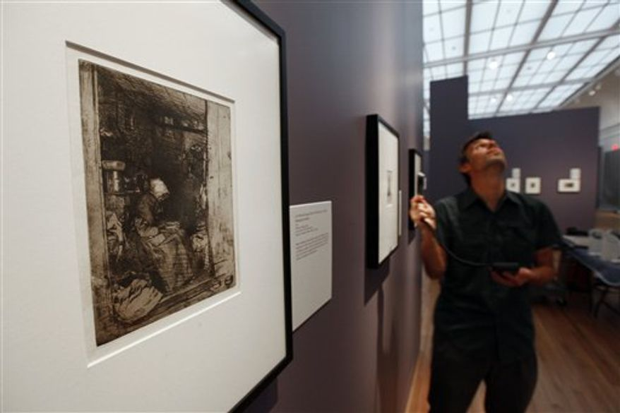 """In this Aug. 18, 2010  photo, technician Matt Casadonte checks lighting levels on prints from 19th Century American artist James McNeill Whistler during installation of the exhibition entitled """"On Beauty and the Everyday: The Prints of James McNeill Whistler"""" at the University of Michigan Museum of Art in Ann Arbor, Mich. (AP Photo/Paul Sancya)"""