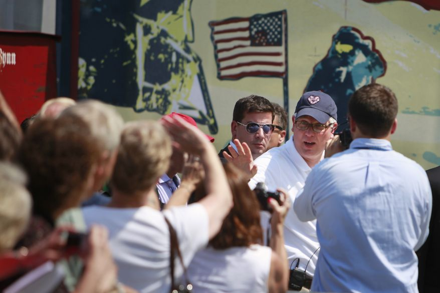 By a image of Neil Armstrong, Glenn Beck, right, waves to supporters at the site of the Restoring Honor rally by the Lincoln Memorial in Washington, on Friday, Aug. 27, 2010. The rally will take place on Saturday. (AP Photo/Jacquelyn Martin)