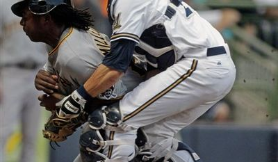Milwaukee Brewers catcher Jonathan Lucroy, right, cannot hold on to the ball as he collides with Pittsburgh Pirates' Lastings Milledge at home during the second inning of a baseball game Friday, Aug. 27, 2010, in Milwaukee. Milledge scored from second on a hit by Ronny Cedeno. (AP Photo/Morry Gash)