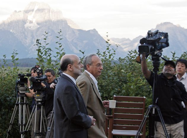 Federal Reserve chairman Ben Bernanke, left, and Donald L. Kohn, governor of the Federal Reserve Bank of Dallas, walk along the veranda of the Jackson Lake Lodge with the Grand Tetons in the distance, Friday, Aug. 27, 2010, at the start of the annual Federal Reserve conference in Jackson,