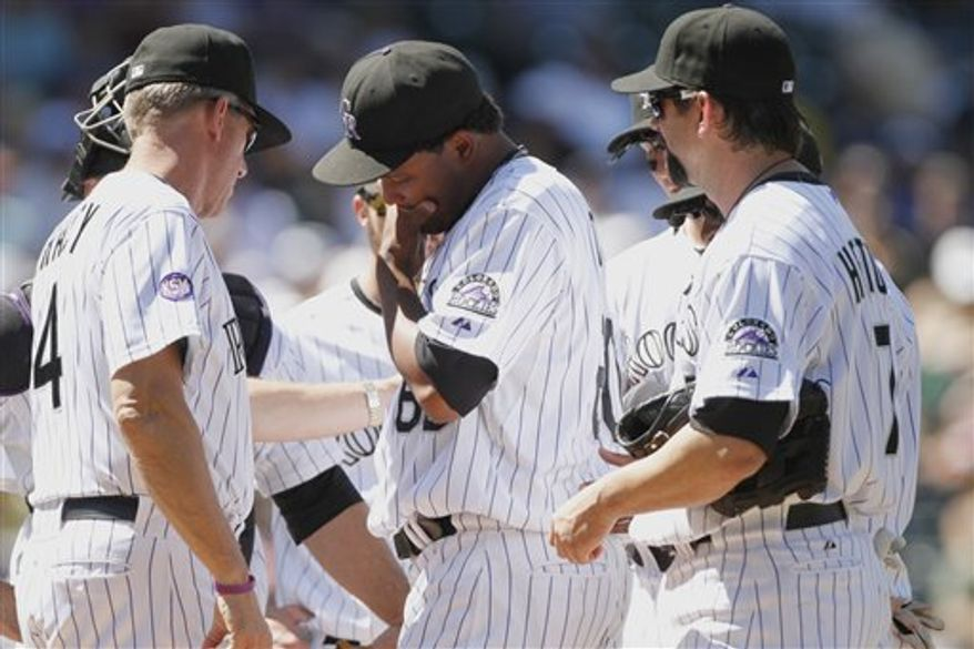Colorado Rockies manager Jim Tracy (4), left,  takes relief pitcher Manny Corpas, center, out of the game after pitching just 1.1 innings during a baseball game against the Atlanta Beaves at Coors Field in Denver on Wednesday, Aug. 25, 2010. The Rockies swept the Braves in a three-game series, coming back from a nine-run deficit to win 12-10. (AP Photo/Barry Gutierrez)