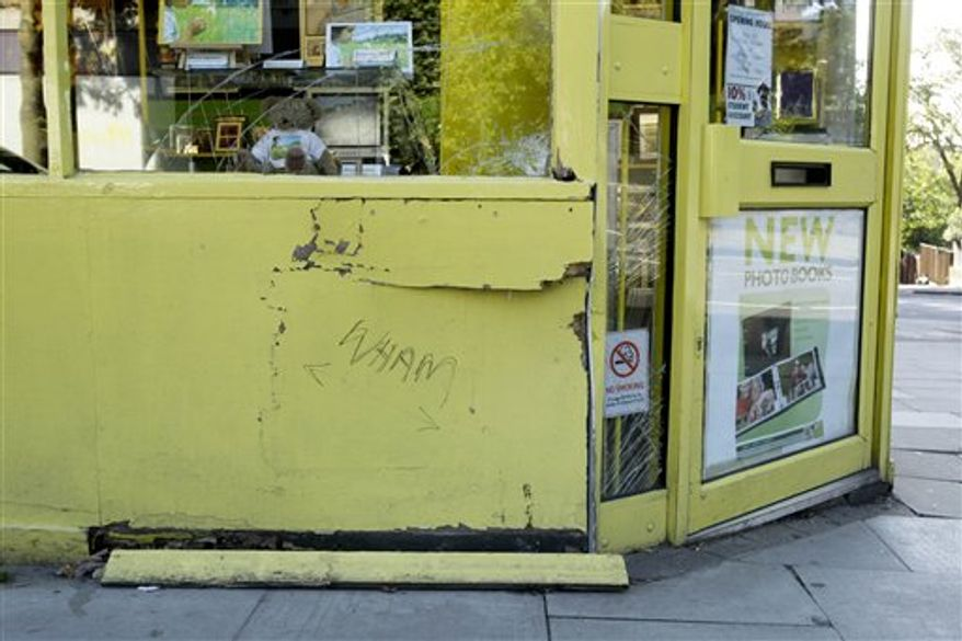 """Damage is seen to wooden panelling and windows on the facade of a branch of the photographic store Snappy Snaps in the Hampstead area of London, following allegations that it was driven into by singer George Michael, Tuesday, Aug. 24, 2010.  Michael is due to appear in court on  Tuesday charged with driving under the influence of drugs following the incident in the early hours of Sunday July 4.  The words """"Wham"""" and """"! By George""""  have since been written on the paneling.  """"Wham!"""" is the name of the pop duo that led to Michael's rise to fame as a singer in the 1980s.  (AP Photo/Matt Dunham)"""