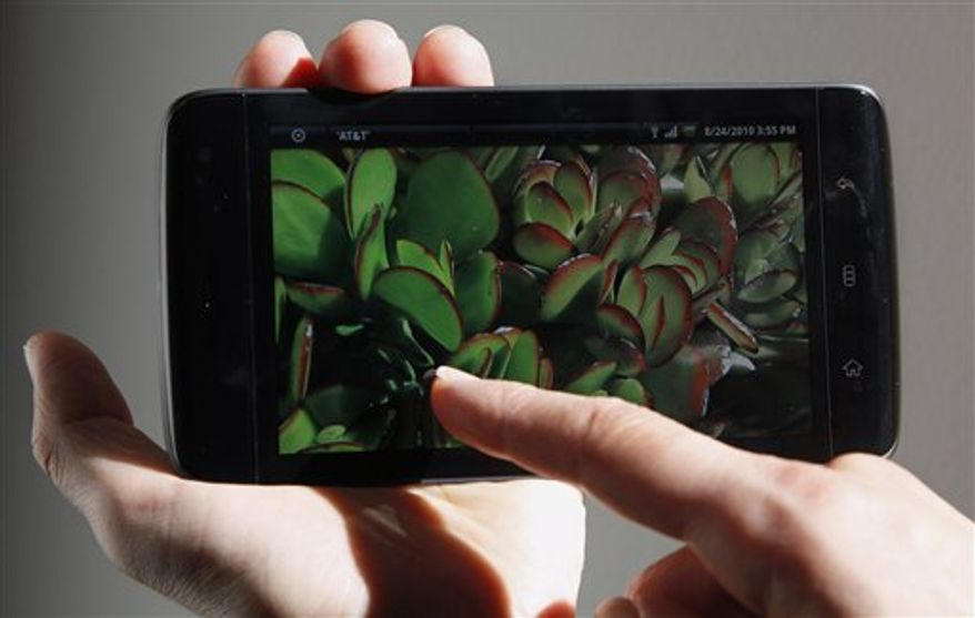 In this Aug. 24, 2010 photo, an Associated Press reporter holds the Dell Streak phone during a product review in San Francisco. (AP Photo/Jeff Chiu)