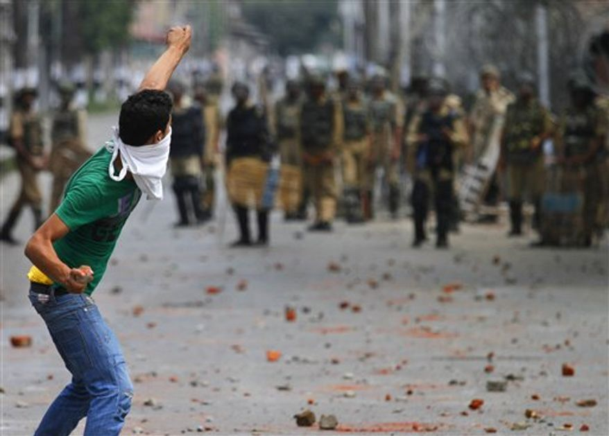 "FILE - In this Wednesday, July  28, 2010 file photo, Kashmiri protesters throw stones on Indian policemen during a protest in Srinagar, India. Ahmed, who calls himself ""an anonymous soldier of Kashmir's resistance movement,"" is part of a wave of Web savvy protesters in Kashmir who have begun using social networking sites to publicize their fight against Indian rule to a global audience and to keep other demonstrators energized and focused. (AP Photo/Mukhtar Khan, File)"