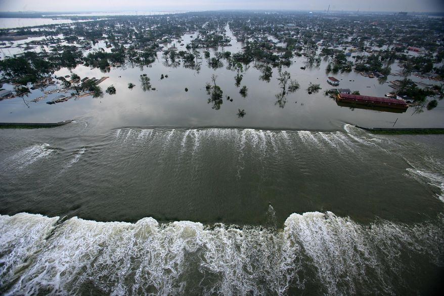 In this Aug. 30, 2005, picture, floodwaters from Hurricane Katrina pour through a levee along Inner Harbor Navigaional Canal near downtown New Orleans, a day after Katrina passed through the city. (AP Photo/Pool, Vincent Laforet)