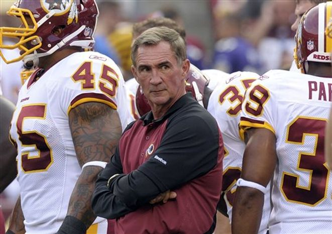 FILE - In this Aug. 15, 2010, file photo, Washington Redskins head coach Mike Shanahan, right, and team owner Daniel Snyder, left, watch practice at the NFL football team's training camp at Redskins Park in Ashburn, Va. Not long after becoming the Redskins' coach, Shanahan invited every team employee _ from marketing executives to secretaries to coaches _ to a meeting. The message: This is a new Redskin Way, and every single person needs to be on board.  (AP Photo/Nick Wass, File)