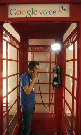 Jason Toff, marketing manager for Google Voice, demonstrates how to make a call from a red phone booth at the Google office in San Francisco, Wednesday, Aug. 25, 2010. Google plans to promote the Google Voice service by setting up red phone booths at universities and airports scattered across the United States. People will be able to make free calls from the booths to U.S. and Canadian numbers and save on international calls.  (AP Photo/Jeff Chiu)