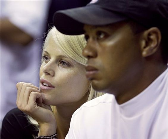 """FILE - In this June 11, 2009 file photo, Elin Nordegren talks to her husband, golfer Tiger Woods during the first quarter of Game 4 of the NBA basketball finals in Orlando, Fla. Nordegren said she has """"been through hell"""" since her husband's infidelity surfaced but she never hit him, according to an interview released Wednesday telling People magazine she and Woods tried for months to reconcile the"""