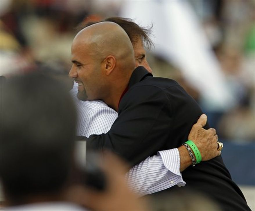 """St. Louis Cardinals baseball player Albert Pujols, foreground, hugs his manager Tony La Russa as he wears his medal at the Glenn Beck """"Restoring Honor"""" rally in front of the Lincoln Memorial in Washington Saturday, Aug. 28, 2010.(AP Photo/Alex Brandon)"""