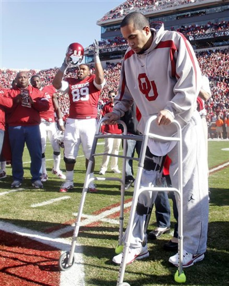 FILE - In this Saturday, Nov. 28, 2009, file photo, Oklahoma defensive tackle Cordero Moore, left, cheers as former Oklahoma receiver Corey Wilson, who injured his back in an off season car accident, climbs out of his wheelchair and takes a few steps with the aid of a walker at the end of Oklahoma's senior day ceremony, before an NCAA college football game against Oklahoma State in Norman, Okla. After he injured his back in a car accide nt, Wilson is now serving as an unofficial assistant coach, helping to review film and offer his teammates pointers.(AP Photo/Sue Ogrocki, File)