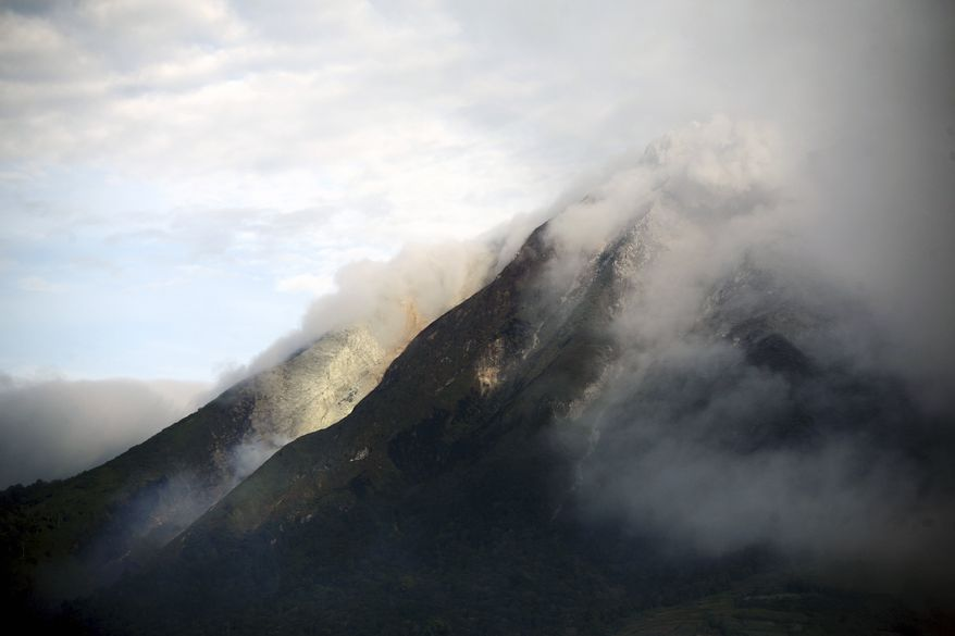 Mount Sinabung spews volcanic smoke high into the sky early Sunday in its first eruption in 400 years, causing thousands of people living around its slope to evacuate their homes in Karo, North Sumatra, Indonesia. (AP Photo/Binsar Bakkara)