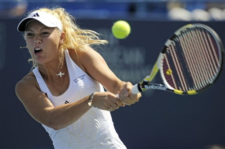 Caroline Wozniacki, of Denmark, lifts her trophy after defeating Nadia Petrova, of Russia, 6-3, 3-6, 6-3, in the women's final of the Pilot Pen tennis tournament in New Haven, Conn., on Saturday, Aug. 28, 2010. (AP Photo/Fred Beckham)