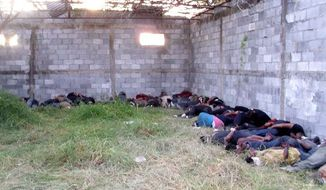 The bodies of the 58 male and 14 female massacre victims are seen inside the abandoned warehouse where they were found in San Fernando in eastern Mexico. They were migrants from Brazil, Ecuador, El Salvador and Honduras trying to get to the United States. (Associated Press)