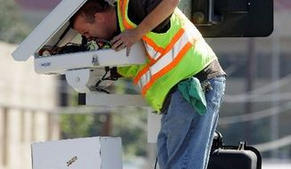 Technician Charles Riggings in March services traffic cameras designed to catch speeders and motorists who run red lights in Los Angeles. (Associated Press)
