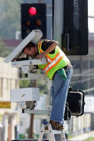 Technician Charles Riggings in March services traffic cameras designed to catch speeders and motorists who run red