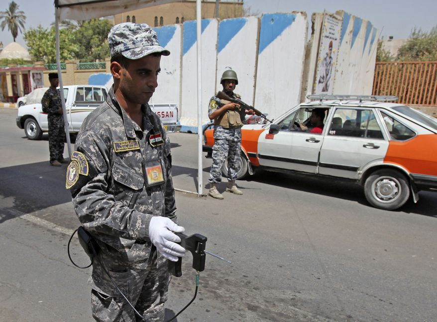 An Iraqi police officer uses a bomb detector at a checkpoint in Baghdad on Sunday, Aug. 29, 2010. (AP Photo/Karim Kadim)