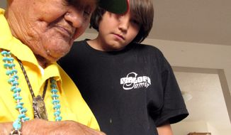 Cpl. Chester Nez, also an Original 29, looks over an old photo with his grandson in Albuquerque, N.M. (Associated Press)