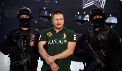 """Federal police stand guard by Texas-born kingpin Edgar """"La Barbie"""" Valdez during his presentation to the press in Mexico City on Tuesday. Valdez, who was captured on Monday by federal police, faces drug-trafficking charges in the U.S. and has been blamed for a vicious turf war that has included bodies hung from bridges and shootouts in central Mexico. Some of that violence has spilled over the border. (Associated Press)"""