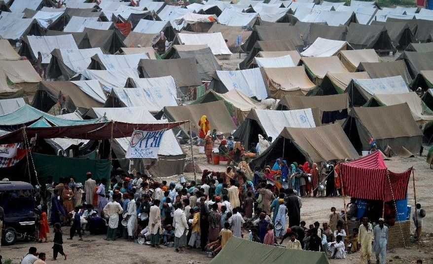 TENT CITY: Pakistani families gather to get the evening meal from a food-distribution point in a camp for flood-affected people in Sukkur, Pakistan, on Tuesday. (Associated Press)