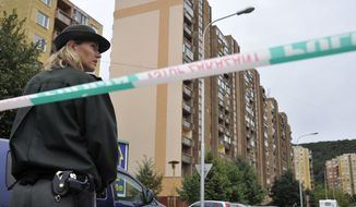 A Slovakian policewoman secures the building where a man identified by authorities as 48-year-old Lubomir Harman opened fire, killing six people and wounding more than a dozen in a Bratislava suburb on Monday, Aug. 30, 2010. (AP Photo/Bela Szandelszky)
