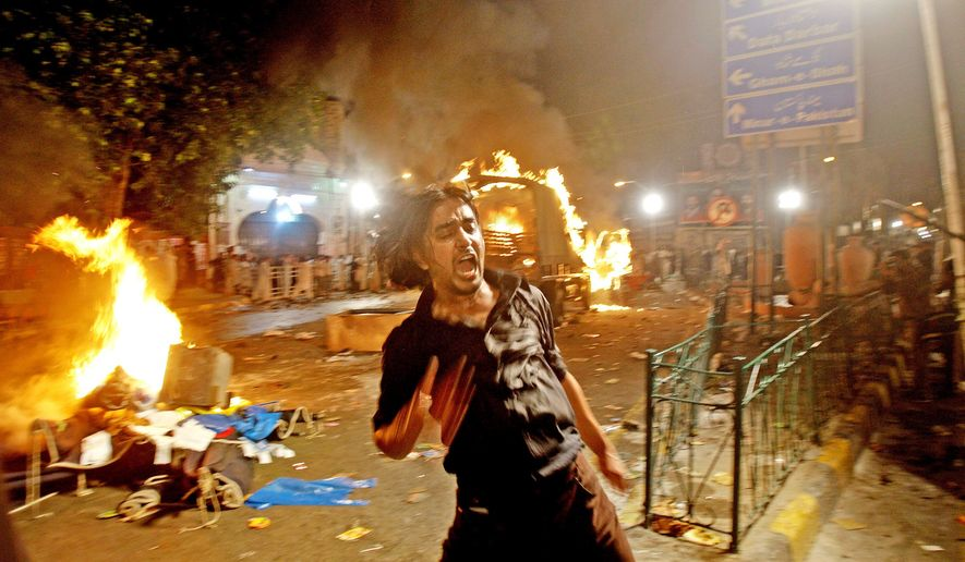 A man attempts to escape from explosions as protesters burn vehicles in Lahore, Pakistan, on Wednesday. Three suicide bombs ripped through a Shiite Muslim religious procession in the eastern Pakistani city of Lahore, police said. Prime Minister Yousuf Raza Gilani condemned the blasts and said the attackers would not escape justice. (Associated Press)