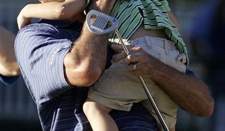 Matt Kuchar hugs his son Cameron, 2, after defeating Martin Laird, of Scotland, on a sudden death playoff hole during the final round of The Barclays golf tournament, Sunday, Aug. 29, 2010, in Paramus, N.J. Kutcher won with a score of 12 under. (AP Photo/Rich Schultz)