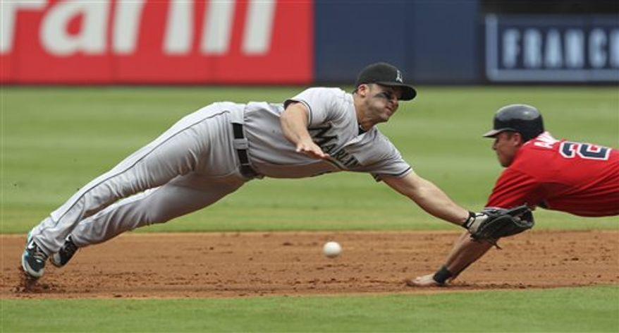Florida Marlins second baseman Dan Uggla, left, dives for the ball as Atlanta Braves' Rick Ankiel, right, steals second base in the first inning of a baseball game in Atlanta, Sunday, Aug. 29, 2010. (AP Photo/John Bazemore)