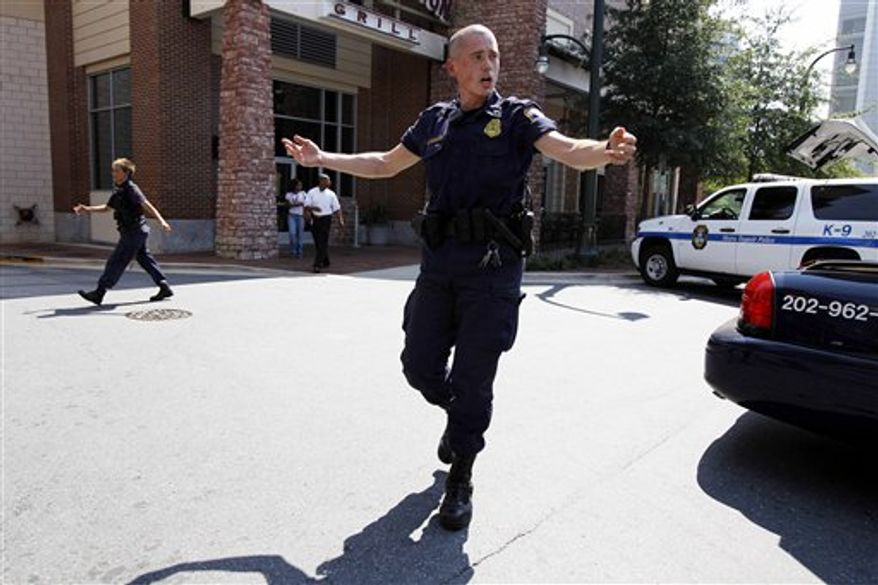 Police push people back from near the front of the headquarters of the Discovery Channel networks building in Silver Spring, Md., Wednesday Sept. 1, 2010. Police say a gunman has taken at least one person hostage in the building.  (AP Photo/Jose Luis Magana)
