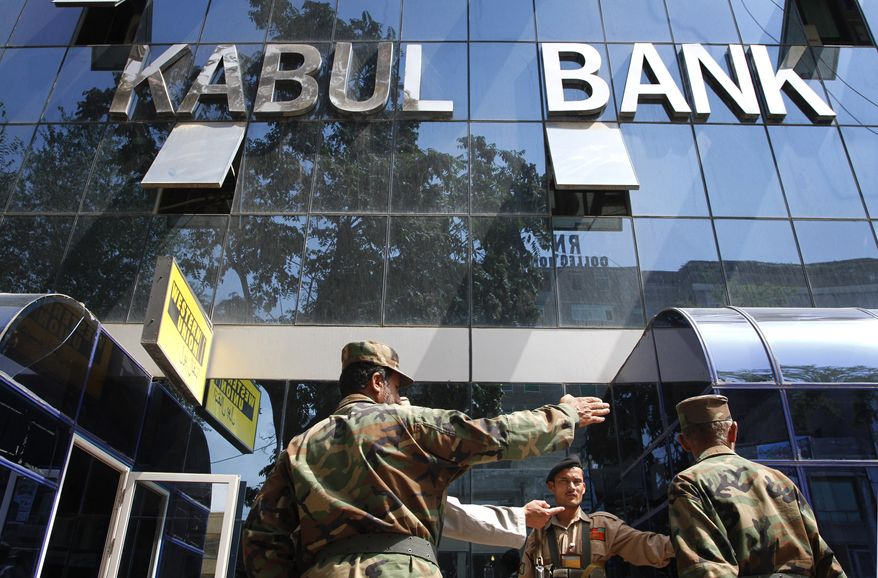 Afghan soldiers chat in front of the main office of Kabul Bank in Kabul, Afghanistan, on Wednesday, Sept. 1, 2010. The Afghan central bank's decision to force out executives of the nation's biggest bank amid allegations of mismanagement and questionable lending practices offers the government a chance to take a strong stand against corruption, the United States said Tuesday. (AP Photo/Musadeq Sadeq)