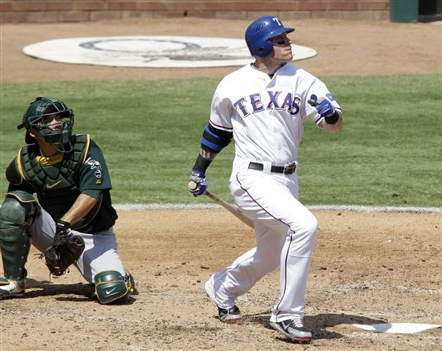 Texas Rangers' Josh Hamilton follows through on a run-scoring single to center in the third inning of a baseball game Sunday, Aug. 29, 2010, in Arlington, Texas. At left is Oakland Athletics catcher Kurt Suzuki. Hamilton drove in the only two runs for Texas in the 8-2 loss to the Athletics. (AP Photo/Tony Gutierrez)