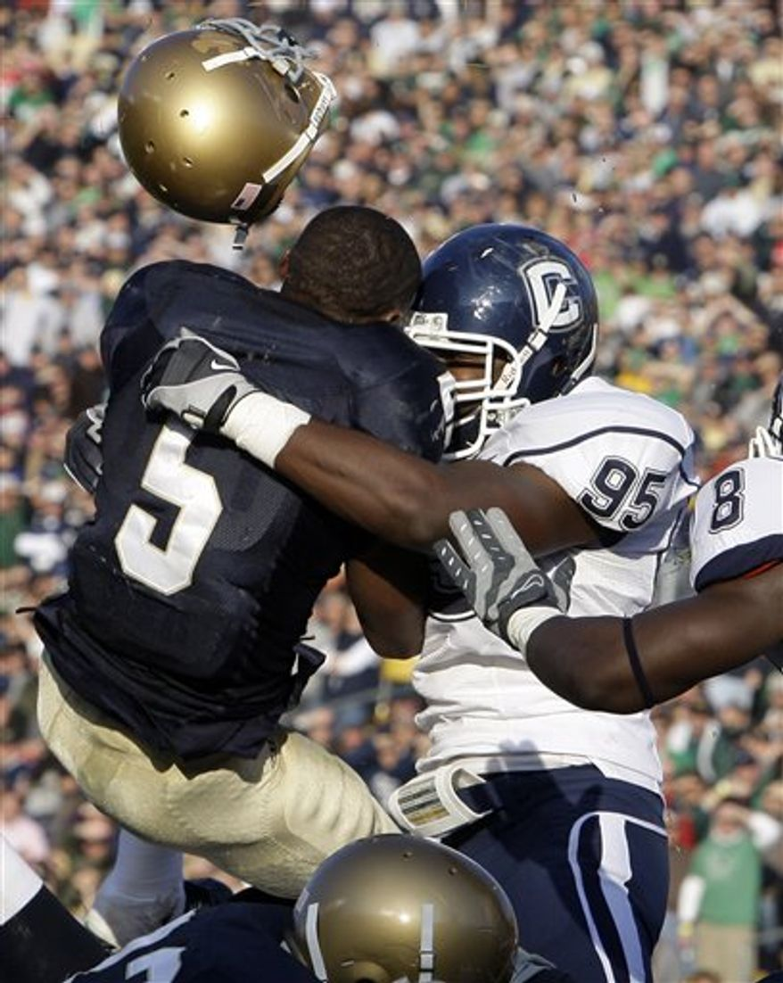 FILE - In this Nov. 21, 2009 file photo, Notre Dame running back Armando Allen Jr., left, loses his helmet as he is hit by Connecticut linebacker Greg Lloyd Jr.,  during the second quarter of an NCAA college football game in South Bend, Ind. Lloyd, who was expected to redshirt the 2010 season while recovering from a knee injury, is slated to start Saturday, Sept. 4, 2010 in the season opener at Michigan.  (AP Photo/Michael Conroy, File)