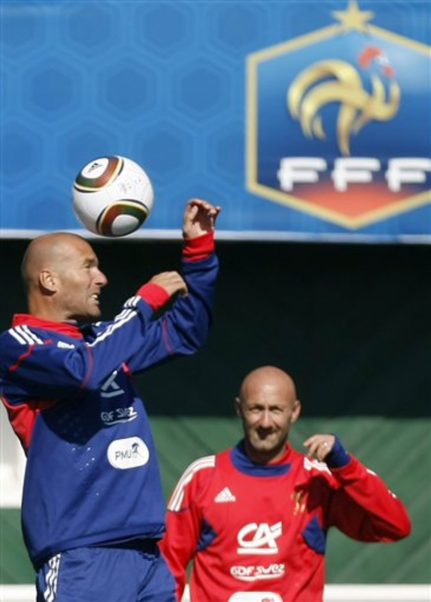 Zinedine Zidane waves with his shoes after his visit to France soccer team players during their training session in Clairefontaine, southwest of Paris Wednesday, Sept 1, 2010 ahead of their opening Euro 2012 qualifiers.(AP Photo/Francois Mori)