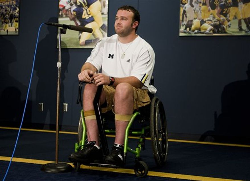 """In this photo taken Aug. 22, 2010, Brock Mealer, brother of Michigan offensive lineman Elliott Mealer, sits in his wheelchair decorated with a """"Michigan"""" sticker, before Michigan's annual NCAA college football media day in Ann Arbor, Mich. Mealer, who is an Ohio State graduate student, has been training with Michigan's strength coaches to recover from a paralyzing car accident in 2008 and strives to lead the Wolverines onto the field for their home opener against Connecticut on Sept. 4, walking without assistance. (AP Photo/Tony Ding)"""