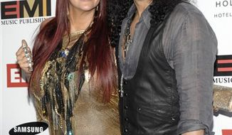 FILE - In this Jan. 31, 2010 file photo, musician Slash, right, and Perla Hudson arrive at the EMI Grammy party in Los Angeles. (AP Photo/Dan Steinberg, file)