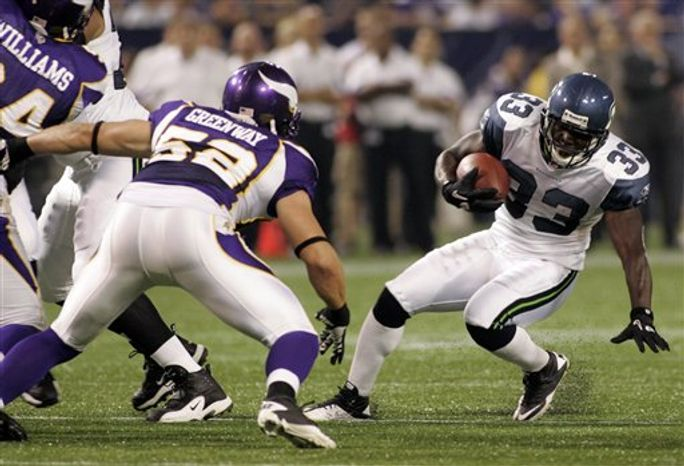 Seattle Seahawks running back Leon Washington (33) runs for a short gain as Minnesota Vikings linebacker Chad Greenway (52) moves in for the tackle during the first half of a preseason NFL football game, Saturday, Aug. 28, 2010, in Minneapolis. (AP Photo/Paul Battaglia)