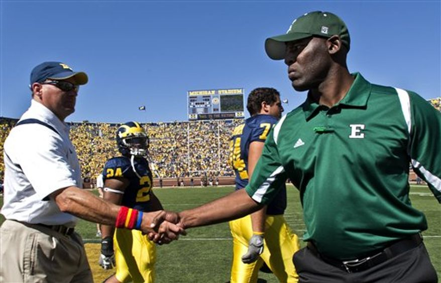 FILE- In this Sept. 19, 2009, file photo, Michigan head coach Rich Rodriguez, left, shakes hands with Eastern Michigan head coach Ron English after an NCAA college football game in Ann Arbor, Mich. English coached under former Michigan head coach Lloyd Carr as the defensive coordinator until Carr's retirement in 2007.  (AP Photo/Tony Ding)