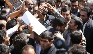 Escorted by his bodyguards, Iranian President Mahmoud Ahmadinejad, right, is greeted by his well wishers, as he attends the annual state-sponsored rally known as Quds Day, or Jerusalem Day, in Tehran, Iran, Friday, Sept. 3, 2010. (AP Photo/Vahid Salemi)