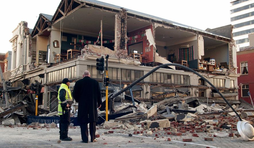 People stand outside a building damaged by a 7.4-magnitude earthquake in central Christchurch, New Zealand, early Saturday, Sept. 4, 2010. A powerful 7.4-magnitude earthquake struck much of New Zealand's South Island early Saturday. No tsunami alert was issued and there were no reports of injuries, but looters broke into some damaged shops in Christchurch, police said. (AP Photo/NZPA, David Alexander)