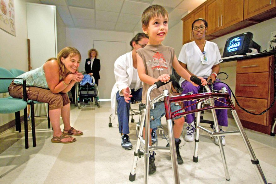 Estelle Soury from St. Jullien L'Ars, France, watches her son, Quentin, take his first steps ever in a biofeedback lab at the Miami Jewish Home and Hospital in Miami. Therapists Maria Verela and Nedgyne Cheremond look on. (Associated Press)