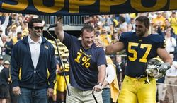 Michigan wide receiver Martavious Odoms (9), quarterback Denard Robinson (16), and coach Rich Rodriguez, right, sing the fight song with teammates and fans after an NCAA college football game with Connecticut, Saturday, Sept. 4, 2010, in Ann Arbor. Michigan won 30-10. (AP Photo/Tony Ding)
