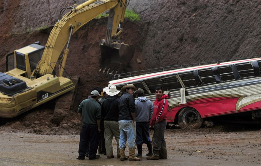 People stand in front of a bus partially covered by a landslide caused by heavy rains on the Pan-American Highway at Tecpan, Guatemala, on Saturday, Sept. 4, 2010. At least 12 passengers were killed and 25 injured, rescue workers said. (AP Photo)