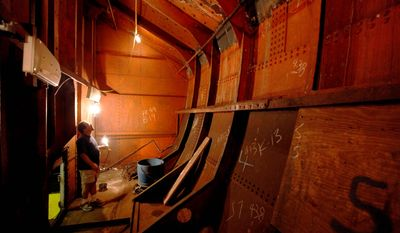 Jesse Lebovics, longtime caretaker of the 1892 USS Olympia, the oldest steel warship still afloat, illuminates a coal bunker to show multiple repairs at and below the waterline. The museum ship, in the Delaware River, needs $1 million to survive. (Associated Press)