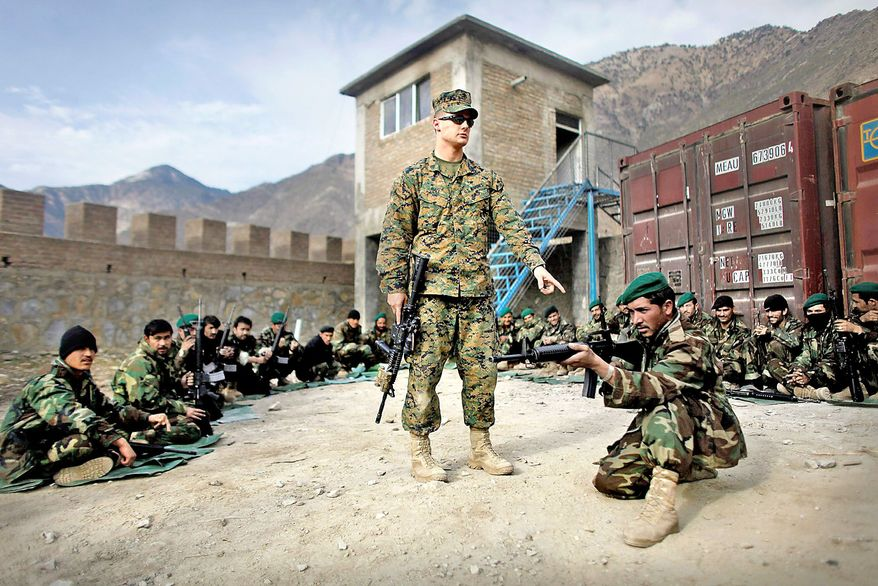 TAKING AIM: Marine Sgt. Terry L. Hall teaches the correct shooting position to Afghan National Army troops at Forward Operating Base Blessing in Kunar province, Afghanistan, in December. (Associated Press)