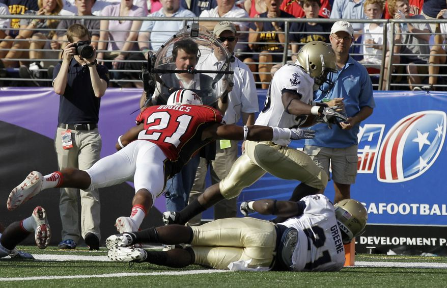 ASSOCIATED PRESS Navy Midshipmen running back Andre Byrd, right, scores a touchdown in front of Maryland defensive back Trenton Hughes (21) as Navy's Gee Gee Greene (21) blocks during the first half of an NCAA college football game, Monday, Sept. 6, 2010, in Baltimore.