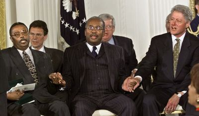 ** FILE ** Jefferson Thomas (left), Ernest Green (center) and President Bill Clinton sing together at the conclusion of a Congressional Gold Medal ceremony at the White House to honor Mr. Thomas, Mr. Green and the other members of the Little Rock Nine, the black students who integrated Little Rock Central High School in 1957.