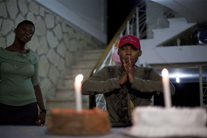 In this July 6, 2010 photo, Bazelais Suy, center, cries in front of his cakes during his birthday party in Port-au-Prince, Haiti. Suy is a student activist whose spine was crushed when a university building collapsed in Haiti's catastrophic earthquake last January. He was airlifted to Chicago for six months of intensive rehabilitation and returned to Haiti with hopes of helping rebuild the country. (AP Photo/Ramon Espinosa)