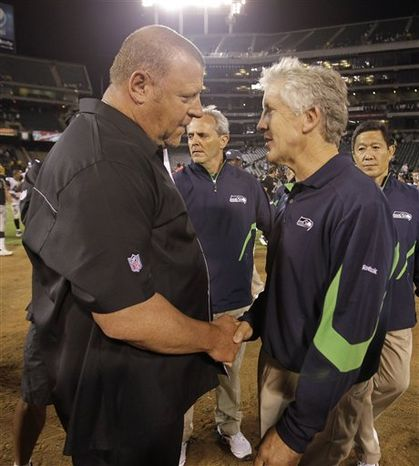 Oakland Raiders head coach Tom Cable, left, shakes hands with Seattle Seahawks head coach Pete Carroll, right, after the Raiders defeated the Seahawks 27-24 in an NFL preseason football game in Oakland, Calif., Thursday, Sept. 2, 2010. (AP Photo/Pa