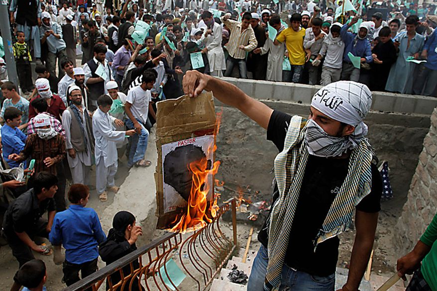 An Afghan protester burns a portrait of Dove World Outreach Center's pastor Terry Jones during a demonstration against the United States, in Kabul, Afghanistan, Monday, Sept. 6, 2010. Hundreds of Afghans railed against the U.S. and called for President Barack Obama's death at a rally in the capital Monday to denounce the American church's plans to burn the Islamic holy book on 9/11. (AP Photo/Musadeq Sadeq)